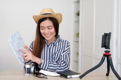Portrait of young asian woman travel blogger holding map while r. Ecording video, live streaming, on social media, blogger and vlogger concept royalty free stock photos