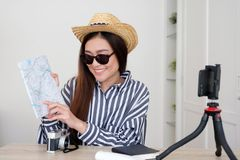 Portrait of young asian woman travel blogger holding map while recording video, live streaming, on social media, blogger and. Vlogger royalty free stock photo