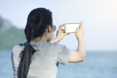 Portrait of young asian woman using smart phone at beach.technology concept.blurred beach sea background.clipping path included Royalty Free Stock Photography
