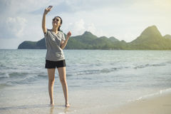 Portrait of young asian woman using smart phone at beach.technology concept.blurred beach sea background. stock photos