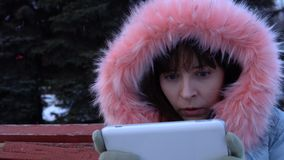 A young woman in a warm jacket uses a digital tablet in the park in the winter. Portrait of a young astonished woman uses a digital tablet and sitting on a stock video footage