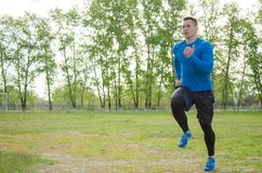 Portrait of a young athlete running across a green field stock images