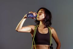Portrait of young athletic and fit Asian Korean woman in fitness top holding bottle drinking water with skipping rope hanging on h stock images