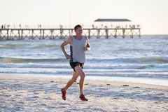 Athletic fit and strong runner man training on Summer sunset beach in sea shore running and fitness workout in sport and healthy l. Portrait of young athletic Royalty Free Stock Photography