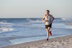 Athletic fit and strong runner man training on Summer sunset beach in sea shore running and fitness workout in sport and healthy l. Portrait of young athletic Stock Images