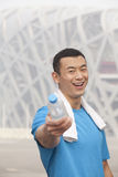 Portrait of young athletic man in Beijing pointing water bottle Stock Images