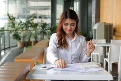 Portrait of young attraction Asian business woman looking his work at coffee cafe in break time. Royalty Free Stock Photography