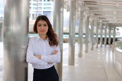 Portrait of young attractive Asian business woman leaning a pole in urban building background.  stock photos