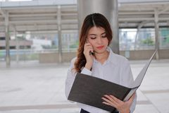 Portrait of young attractive Asian business woman talking on phone for his work at urban outdoor background. Royalty Free Stock Images