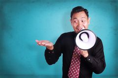 Young Man Shouting with Megaphone, Promotion Concept. Portrait of young attractive Asian businessman shouting with megaphone while showing something on his open Royalty Free Stock Photo