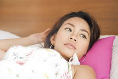 Portrait of young attractive and beautiful Asian woman lying on bed at bedroom in sweet expression. Portrait of young attractive and beautiful Asian woman lying Royalty Free Stock Images