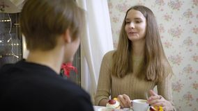 Portrait of young attractive brunette. Beautiful girl sitting in a cafe with my boyfriend and flirty talks with him stock video footage