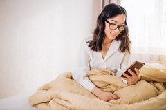 Beautiful young smiling brunette woman using phone in her bedroom. Portrait of young attractive brunette with glasses dressed in white shirt sitting on bed in stock photo