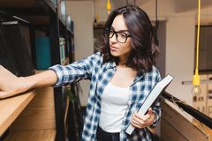 Portrait young attractive brunette woman in black glasses in library looking for books. Smart student, studying time. Good work, academic stock photo