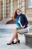 Portrait of young attractive brunette woman with glasses reading book Royalty Free Stock Photography