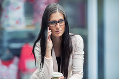 Portrait of young attractive business woman standing in the shopping mall with coffee and using her cell phone. Business break. Royalty Free Stock Photos