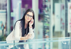 Portrait of young attractive business woman standing in the shopping mall with coffee and using her cell phone. Business break. Stock Photos