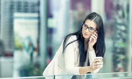 Portrait of young attractive business woman standing in the shopping mall with coffee and using her cell phone. Business break. Stock Images