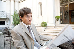 Businessman reading paper in cafe. Stock Image