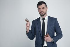 Portrait of young attractive businessman with serious and confident look, holding wooden comb. Stylish bearded barber in suit stock photo