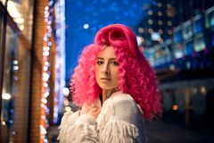 Portrait young attractive caucasian girl model with afro style curly bright pink hair, tattooed face. Evening downtown walking.  stock image