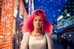 Portrait young attractive caucasian girl model with afro style curly bright pink hair, tattooed face. Evening downtown walking.  stock images