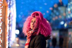 Portrait young attractive caucasian girl model with afro style curly bright pink hair, tattooed face. Evening downtown walking royalty free stock images