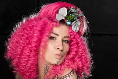 Portrait of young attractive caucasian girl model with afro style curly bright pink hair, tattooed face and flowers woven into her royalty free stock photos