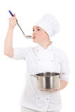Portrait of young attractive cook woman in uniform with pan tasting food isolated on white. Background royalty free stock photo