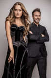Portrait of young attractive couple posing at studio dressed in black fashionable clothes. Royalty Free Stock Images