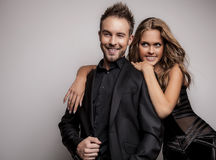 Portrait of young attractive couple posing at studio dressed in black fashionable clothes. Royalty Free Stock Image