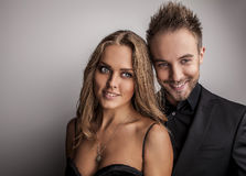 Portrait of young attractive couple posing at studio dressed in black fashionable clothes. Royalty Free Stock Photography