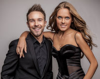 Portrait of young attractive couple posing at studio dressed in black fashionable clothes. Photo Stock Photos