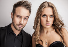 Portrait of young attractive couple posing at studio dressed in black fashionable clothes. Stock Image