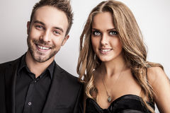 Portrait of young attractive couple posing at studio dressed in black fashionable clothes. royalty free stock photo
