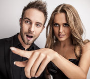 Portrait of young attractive couple posing at studio dressed in black fashionable clothes. Stock Images