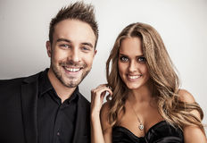 Portrait of young attractive couple posing at studio dressed in black fashionable clothes. Stock Photo