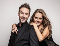 Portrait of young attractive couple posing at studio dressed in black fashionable clothes. Royalty Free Stock Photos
