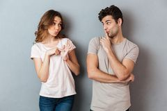 Portrait of a young attractive couple showing peace gesture. And looking at each other over gray wall Stock Images