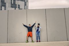 Portrait of young and attractive couple standing in front of the wall. Portrait of young and attractive couple standing in front of the wall in urban park of Royalty Free Stock Image
