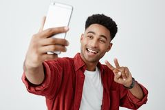 Portrait of young attractive dark-skinned african guy with curly hair in white t-shirt and stylish red shirt talking stock images