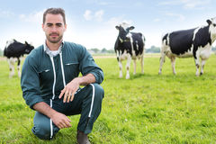 Portrait of a young attractive farmer in a pasture with cows Stock Images