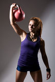 Portrait of young attractive female doing kettle bell exercise o Royalty Free Stock Images