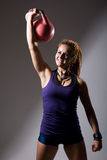 Portrait of young attractive female doing kettle bell exercise o Royalty Free Stock Photography