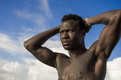 Portrait of young attractive and fit black afro American man with strong muscular body posing cool model attitude on the beach. Close up head and shoulders royalty free stock images