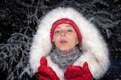 Portrait of young attractive girl in red hat and mittens and  is. Portrait of young attractive girl in red hat and mittens and in fur coat made of artificial fur Stock Photo