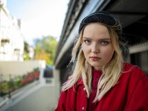 Portrait of a young attractive girl in a red jacket and knitted black jacket under the bridge with a serious face stock images