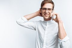 Portrait of young attractive guy in glasses talking on phone and depicting joy, in white shirt isolated on white background, for a royalty free stock images