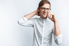 Portrait of young attractive guy in glasses talking on phone and depicting joy, in white shirt isolated on white background, for a stock image