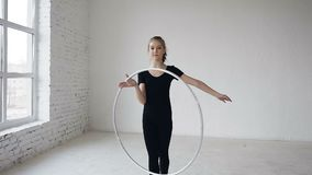 Portrait of young attractive happy girl in black body spinning the hoop on the hand in the gymnastic school at white. Background near big windows and smiling on stock video